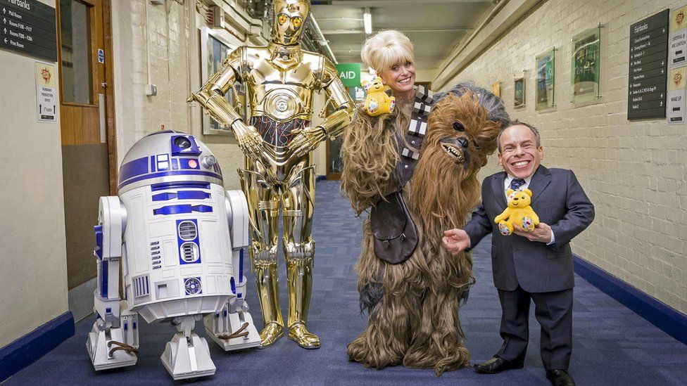 Barbara Windsor with actor Warwick Davis, C-3PO and R2-D2.