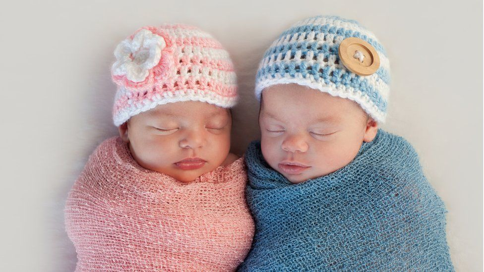 Baby girl and baby boy wrapped up next to each other
