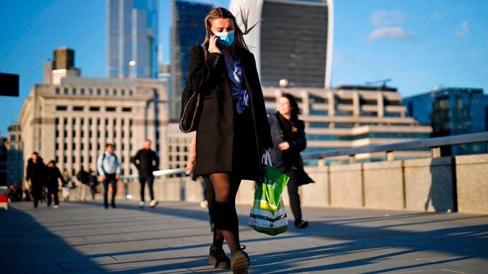 Woman wearing a face mask walks across London Bridge