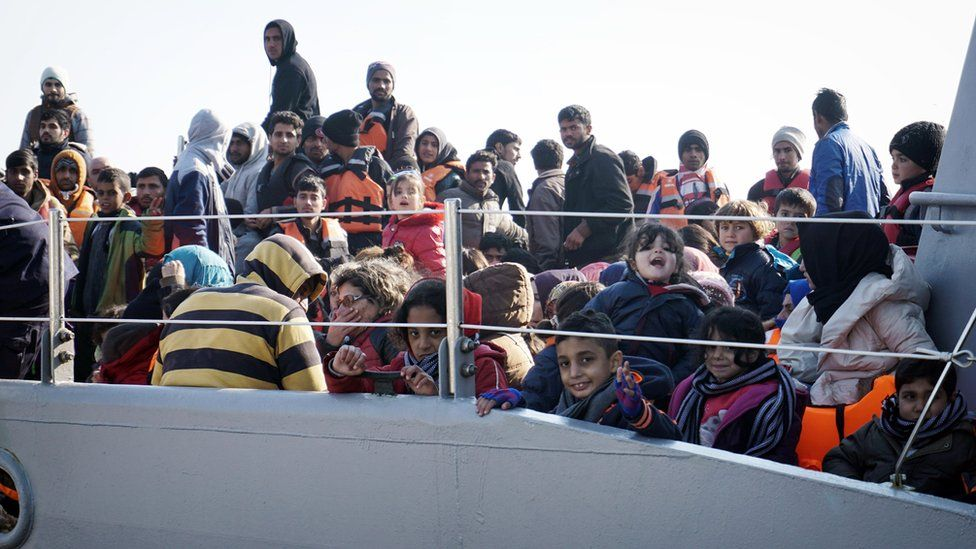 Refugees arrive aboard a Greek coast guard boat on Greek island of Lesbos on March 29, 2016, after being rescued