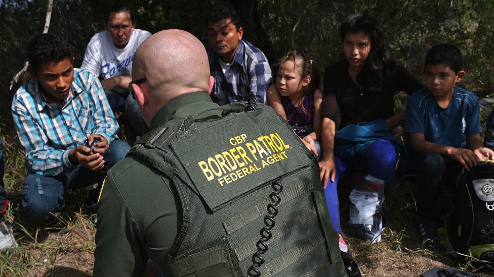 A US Border Patrol agent speaks with Central American migrants who attempted to enter into the US.