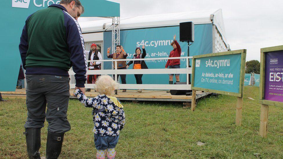 Criw Cyw yn rhoi gwên ar wynebau er gwaetha'r cymylau fore Mawrth. // A wave from S4C's 'Cyw' presenters makes this little lady's day.