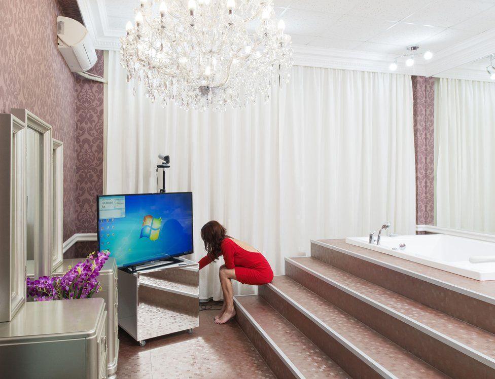 Joven en un baño frente a una gran pantalla de televisión