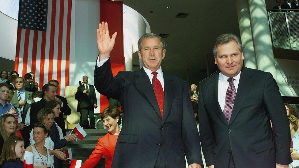 S President George W. Bush (C) waves as he stands next to Polish President Aleksander Kwasniewski(Rt), as Laura Bush greets the crowd to the rear shortly before President Bush delivered a major foreign policy speech on his administration's policies toward Europe at the Universtiy Library 15 June, 2001 in Warsaw, Poland