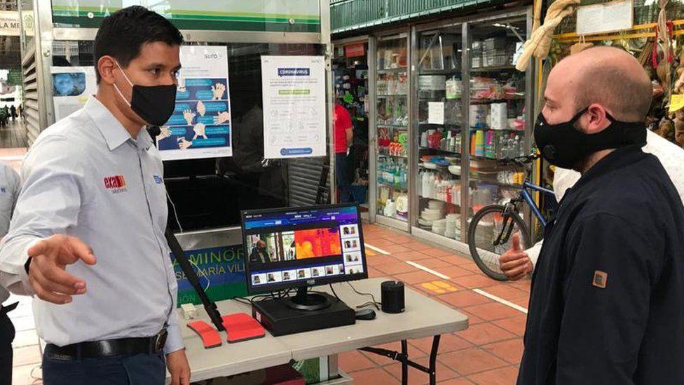 Customers walk past artificial intelligence cameras installed at entrances of Medellín, Colombia's Plaza Minorista market.
