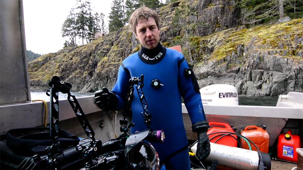 Photographer Tavish Campbell on his boat after diving to gather the effluent footage