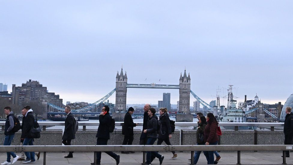 Commuters on a bridge over the River Thames in London