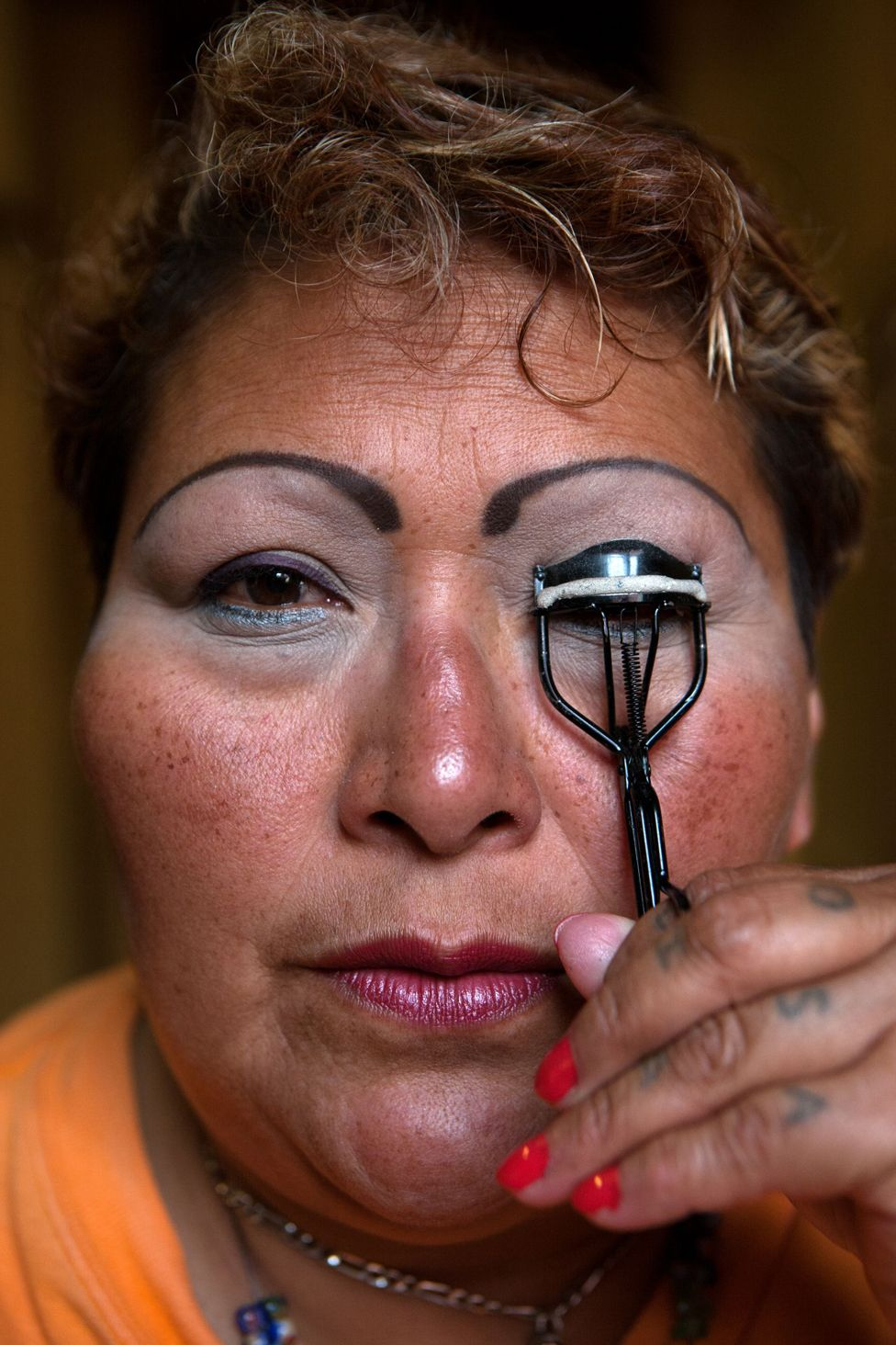 Paola, a resident at Casa Xochiquetzal, puts on make-up before going to work