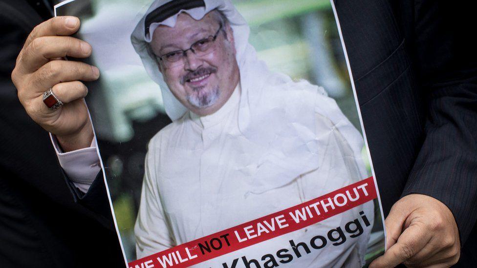 Someone holds up a sign with Khashoggi on it