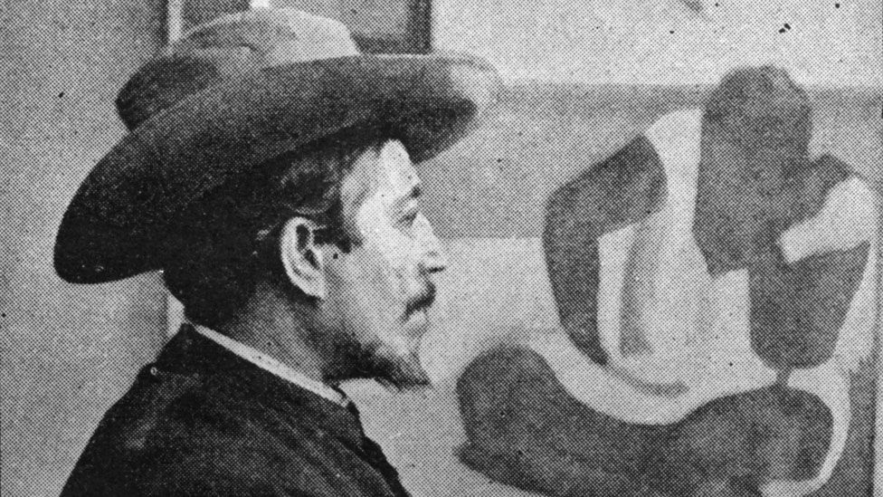 Gauguin pictured with one of his paintings in 1895