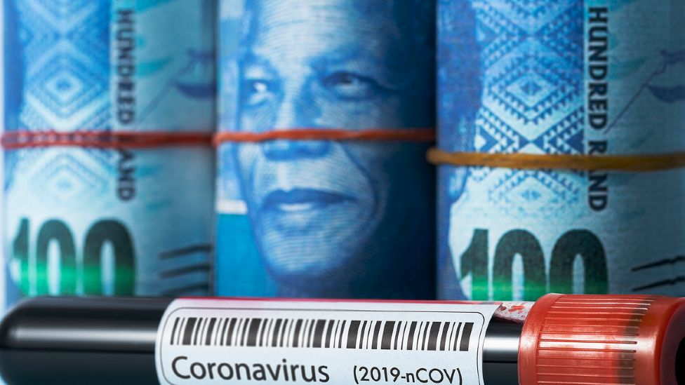 Bundles of South African rand notes showing the face of Nelson Mandela placed behind a vial of blood laballed coroanvirus