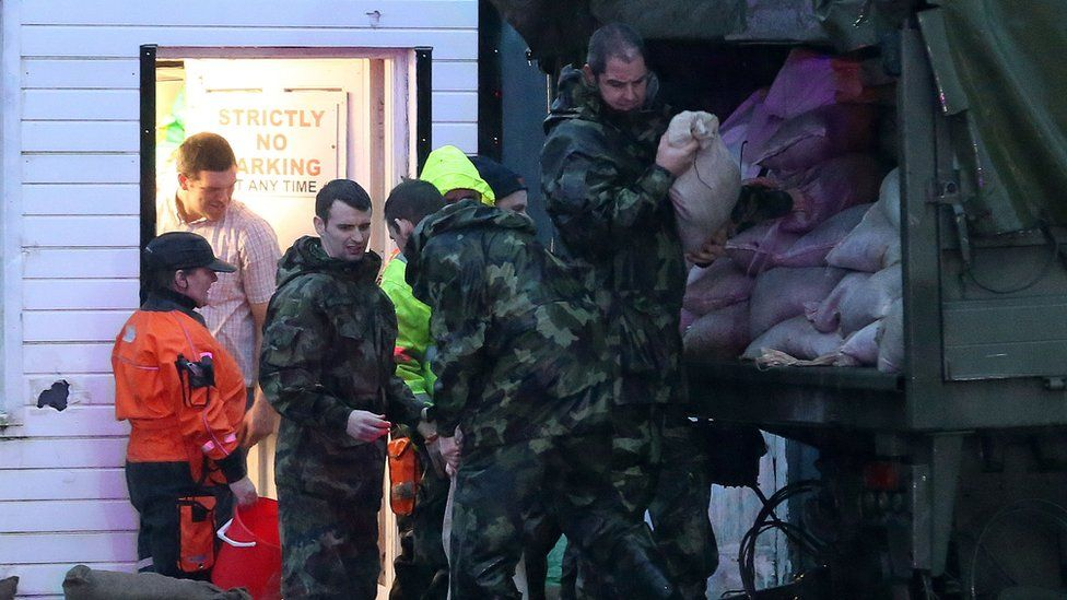 Members of the Army distribute sandbags and bail out water from shops in Donegal