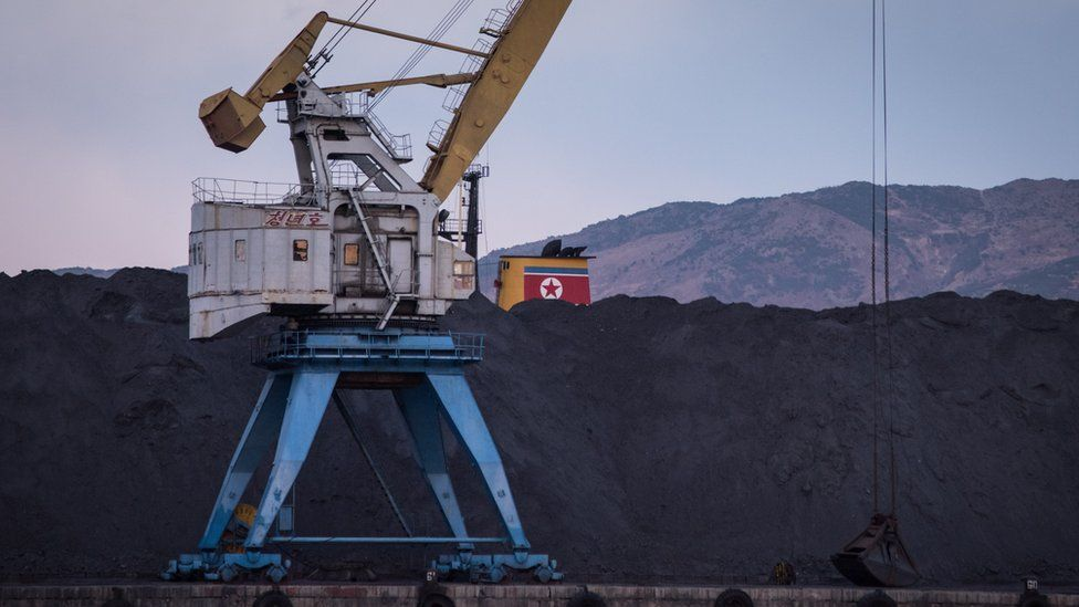 North Korean coal -- which would once have been bound for China -- is piled up on one side of the barrier in Rajin harbour, stranded by a UN ban on coal exports by Pyongyang