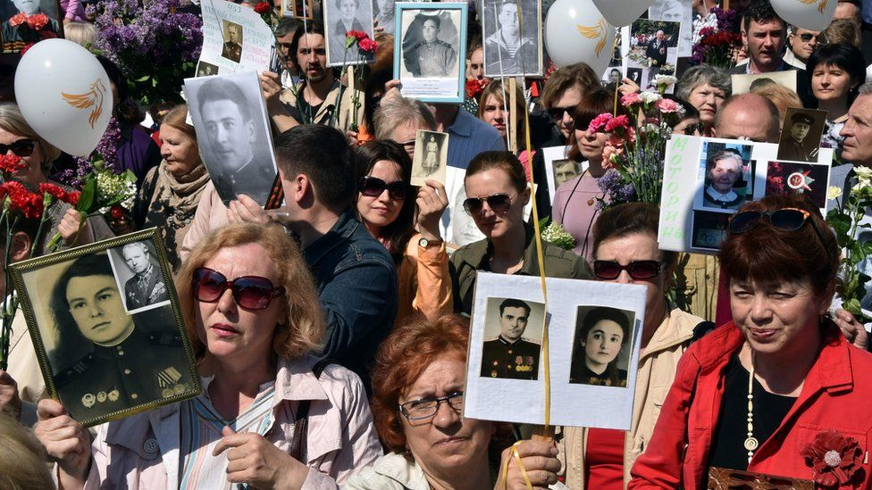 People hold portraits of their relatives and participants during the Immortal Regiment march in the Ukrainian capital of Kiev on May 9, 2016