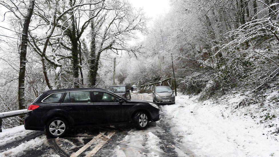 A car turns around after a fallen tree blocks the A40 near Sennybridge, Wales