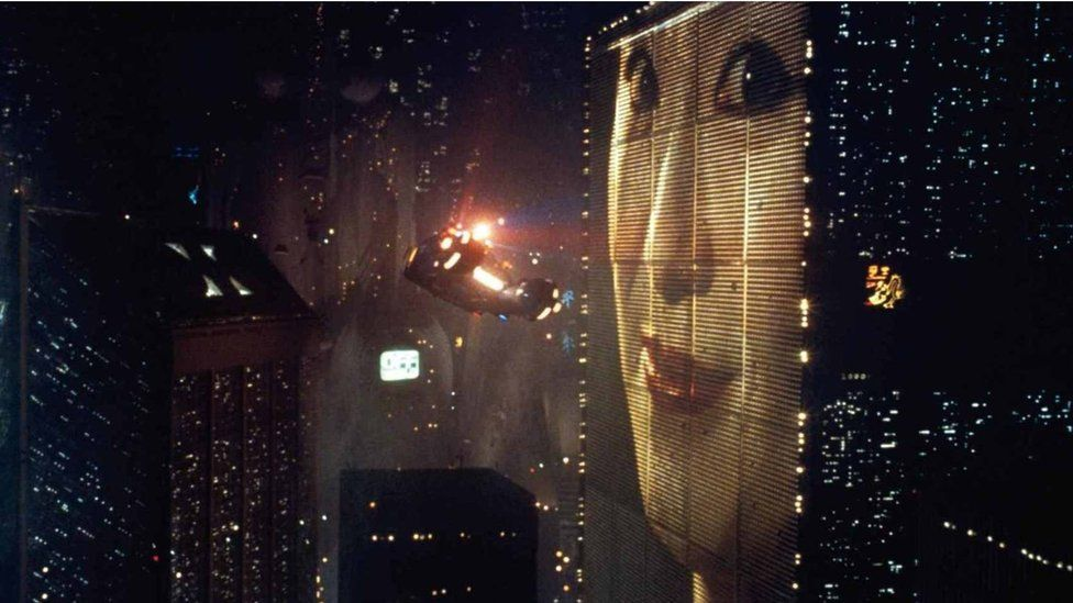 Still from Blade Runner film showing giant advert of Asian woman