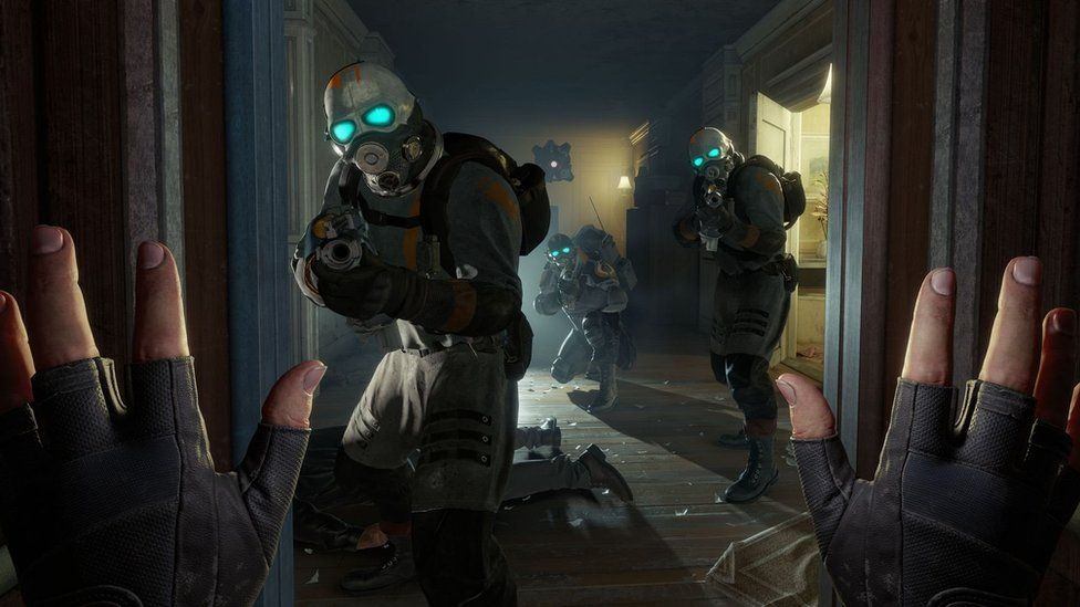 A screenshot from Valve's VR title Half-Life: Alyx, showing a first-person view of someone raising their hands in front of heavily-armed soldiers