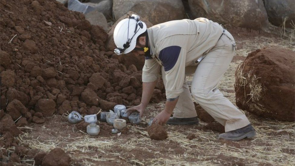 A civil defence member gathers unexploded cluster bombs that activists say were fired by the Russian planes at Maasran, southern Idlib province.