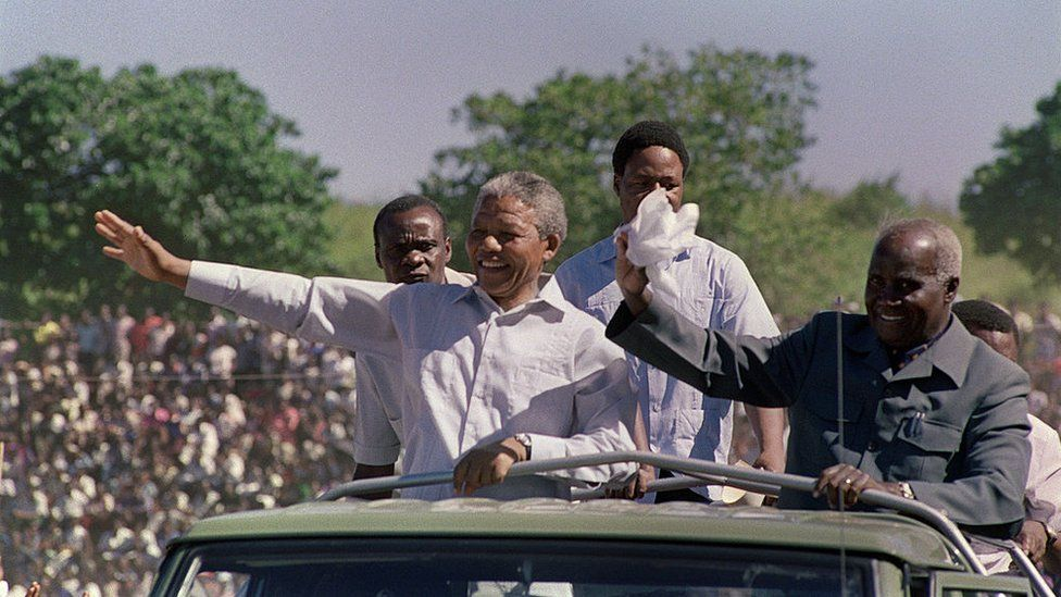 South African anti-apartheid leader and African National Congress (ANC) member Nelson Mandela (L) and Zambian President Kenneth Kaunda (R) wave to the crowd as they arrive at a mass rally of ANC, at Independent Stadium, 03 March 1990 in Lusaka, seat of the exiled ANC. Nelson Mandela, who was released from jail 11 February 1990, is in Zambia to attend a meeting of ANC National Executive Committee