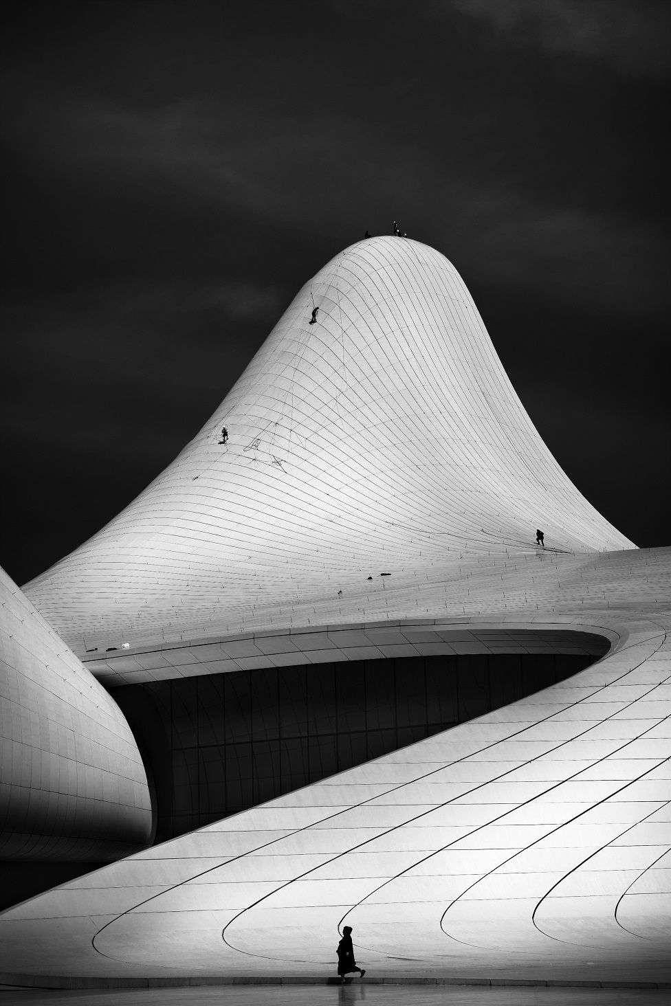 A black and white photo of a curved building