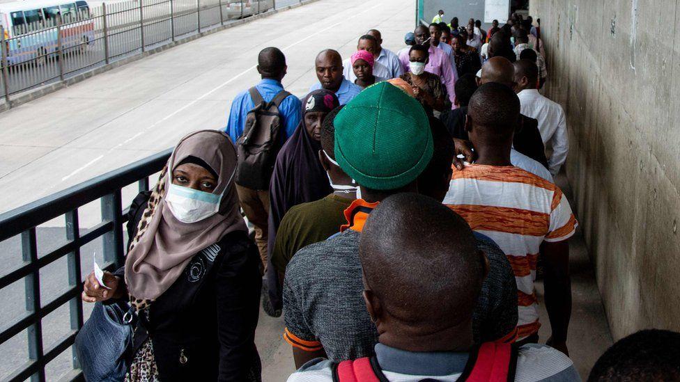 People walk on a pedestrian bridge in Dar es Salaam, Tanzania - 16 April 2020