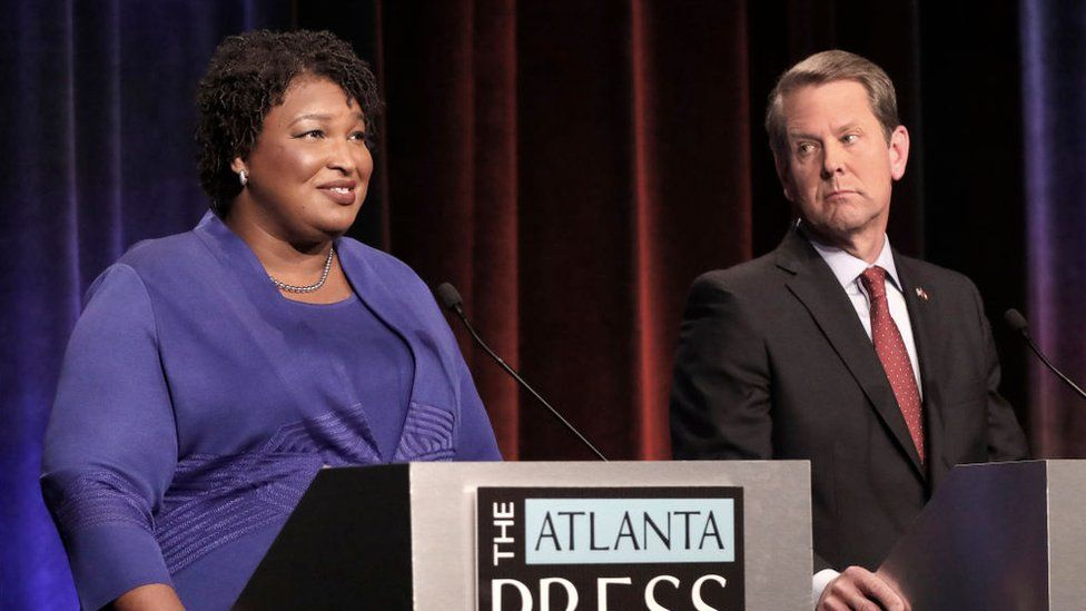 Stacey Abrams (left) and Brian Kemp (right) at a debate.