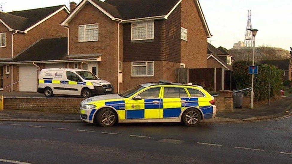 Police vehicles outside a house