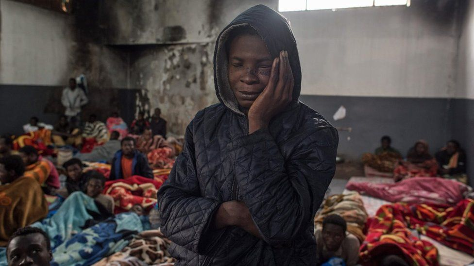 A migrant holds his head as he stands in a packed room at the Tariq Al-Matar detention centre on the outskirts of the Libyan capital Tripoli on November 27, 2017
