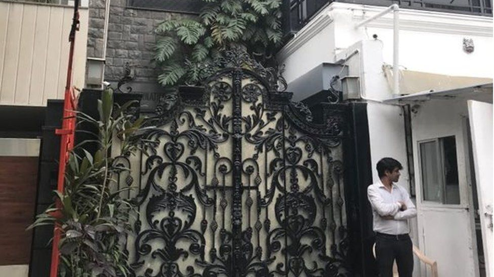 An ornate gate in front of a building