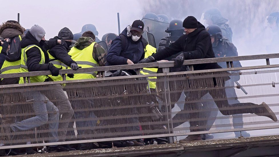 """Former French boxing champion Chistophe Dettinger (C, wearing black hat) kicks a French gendarme on the ground during violent clashes on a pedestrian footbridge, during the """"Gilets Jaunes"""" (Yellow Vests) protest in Paris, France, taken 05 January 2019"""
