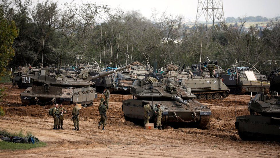 Israeli soldiers stand next to tanks and armoured personnel carriers near the border with Gaza (26 March 2019)