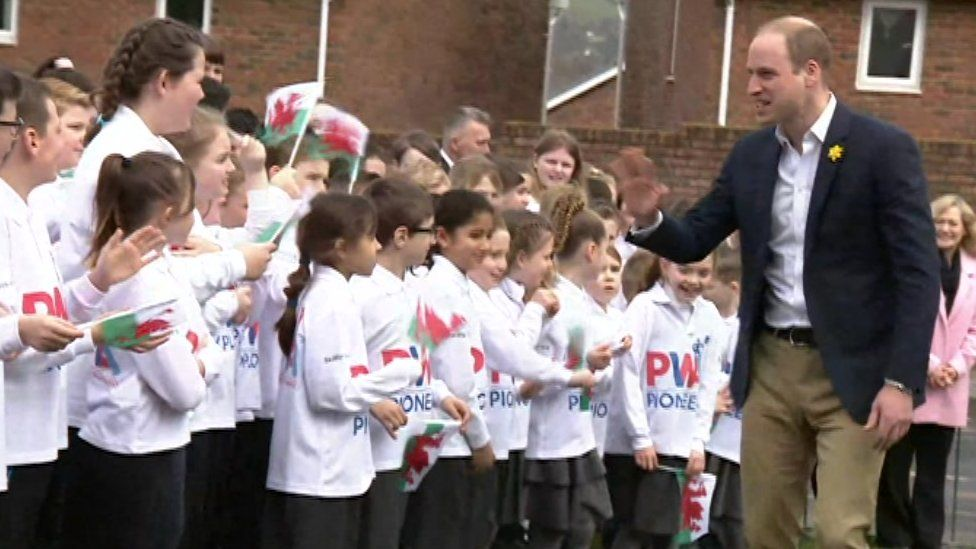 Prince William speaks to schoolchildren as he arrives at the school in Abergavenny