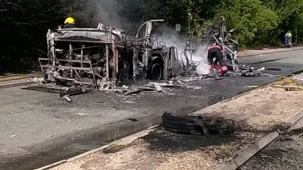 The wreckage of the burnt out bus by the side of the A11