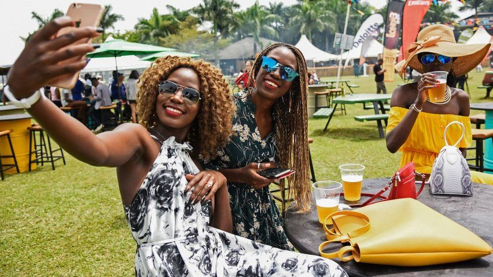 Women take selfie pictures with their mobile phone during the Royal Ascot Goat Races in Kampala, Uganda, on August 25, 2018.