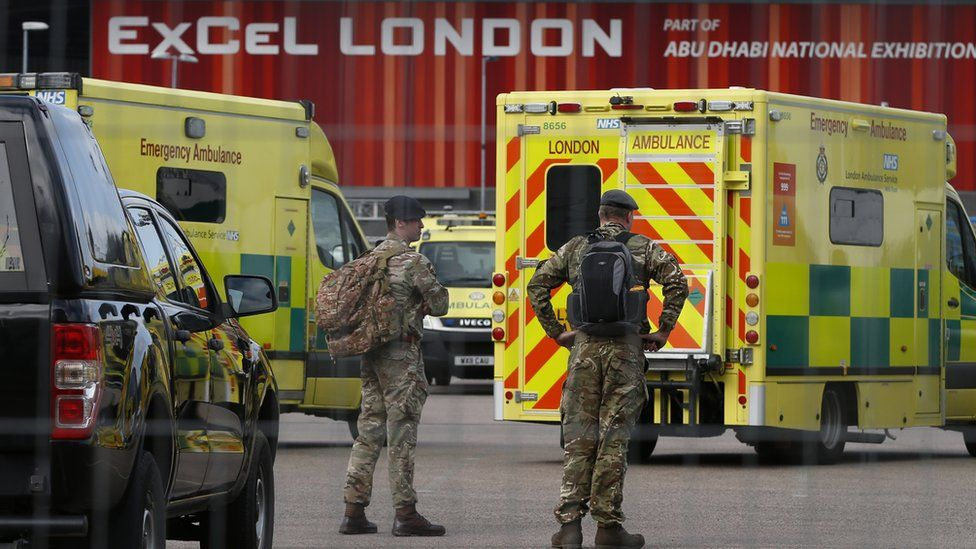 Military personnel stand near London Ambulance Service vehicles at the new NHS Nightingale Hospital at ExCeL London on March 25, 2020 in London, England.