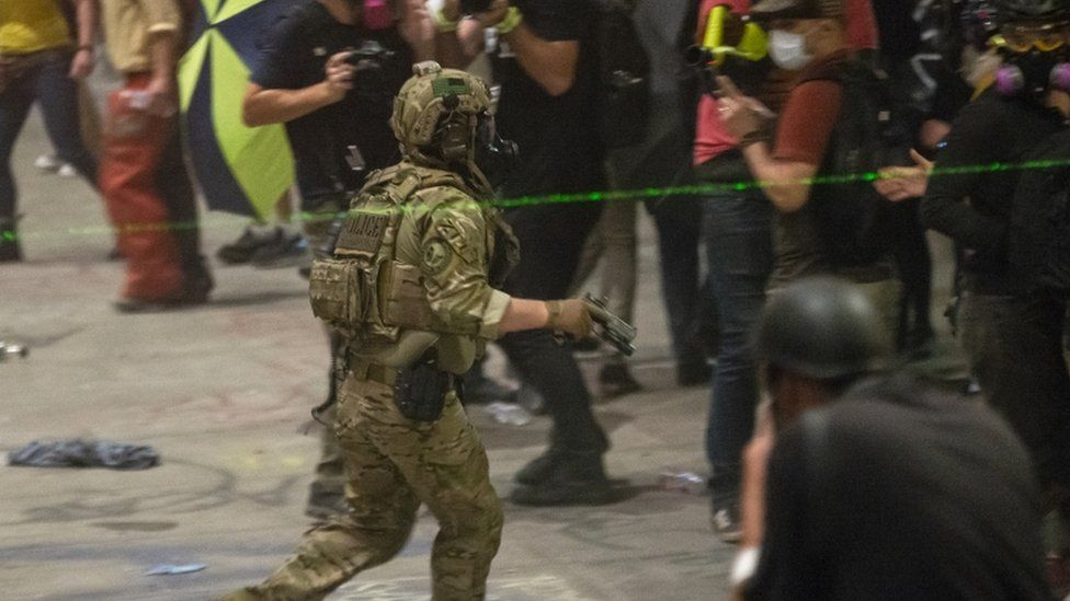 A federal officer with a handheld device attempts to disperse a large crowd 20, July 2020