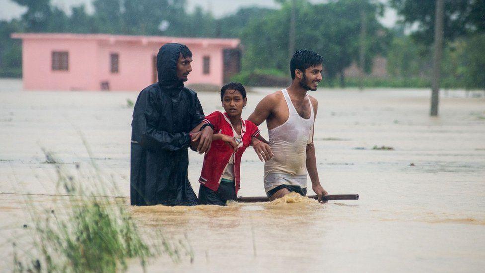 Nepali residents wade along a flood area at Birgunj Parsa district, some 200km south of Kathmandu,