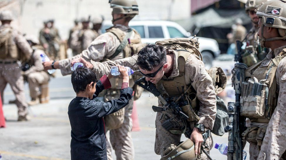 A US Marine and a child spray water at each other during an evacuation at Hamid Karzai International Airport, Kabul, Afghanistan, 21 August 2021
