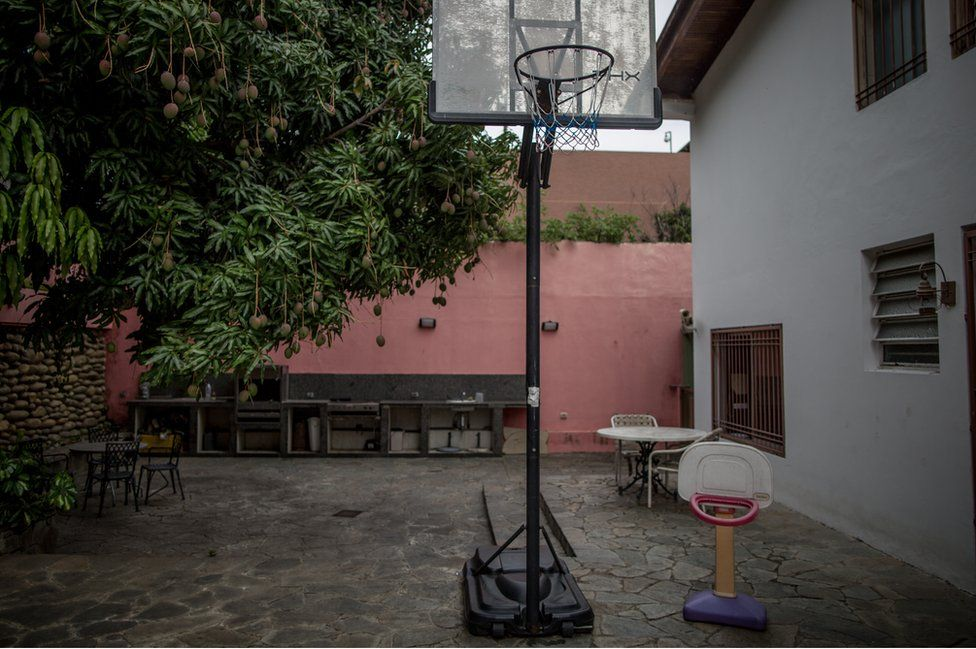 The family mango tree besides a full-size basketball hoop and a tiny one that Juan Pablo played with as a child