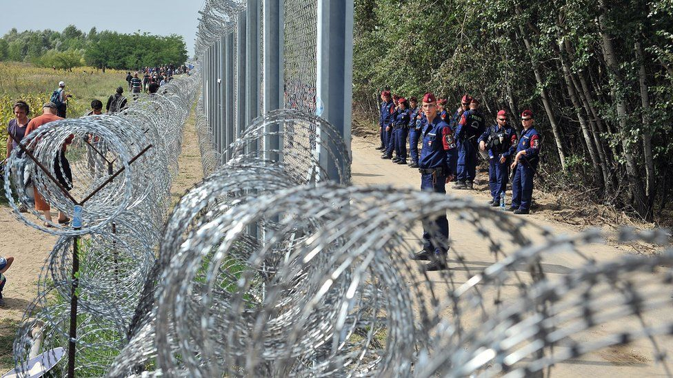 Migrants and refugees walk near razor-wire fence secured by Hungarian police (R) near northern Serbian town of Horgos, 15 Sep 2015