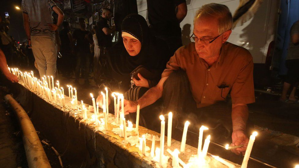 Iraqis light candles following Sunday's deadly suicide attack