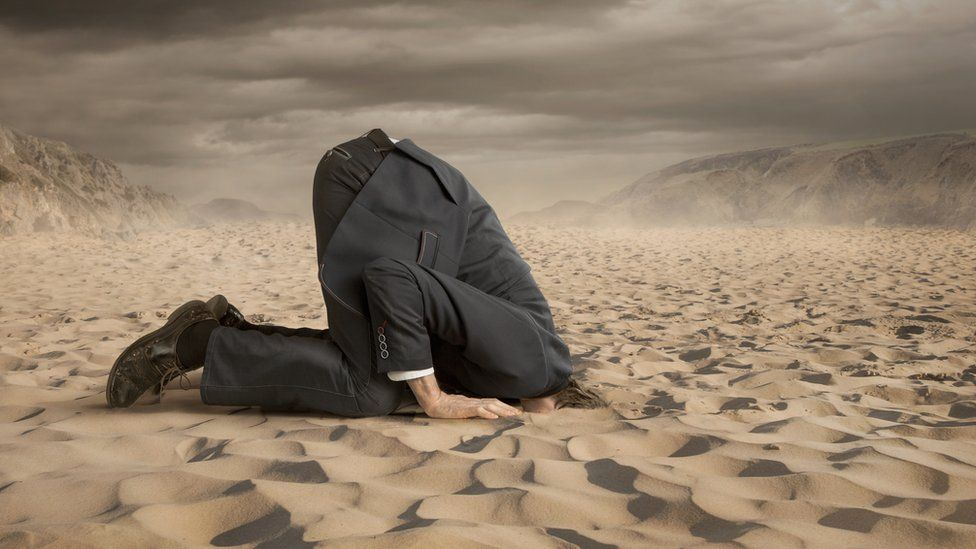 Man with head in sand