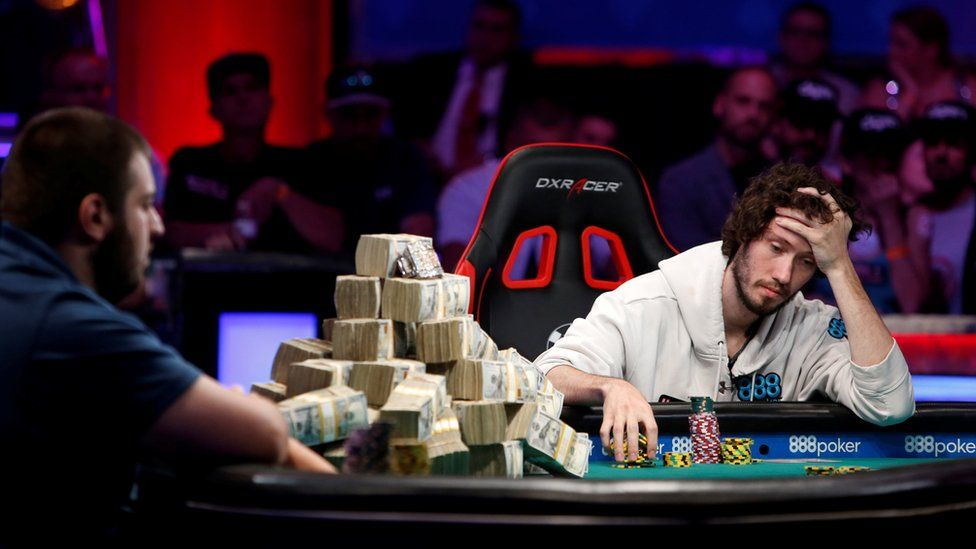 man looking sad next to pile of cash on poker table