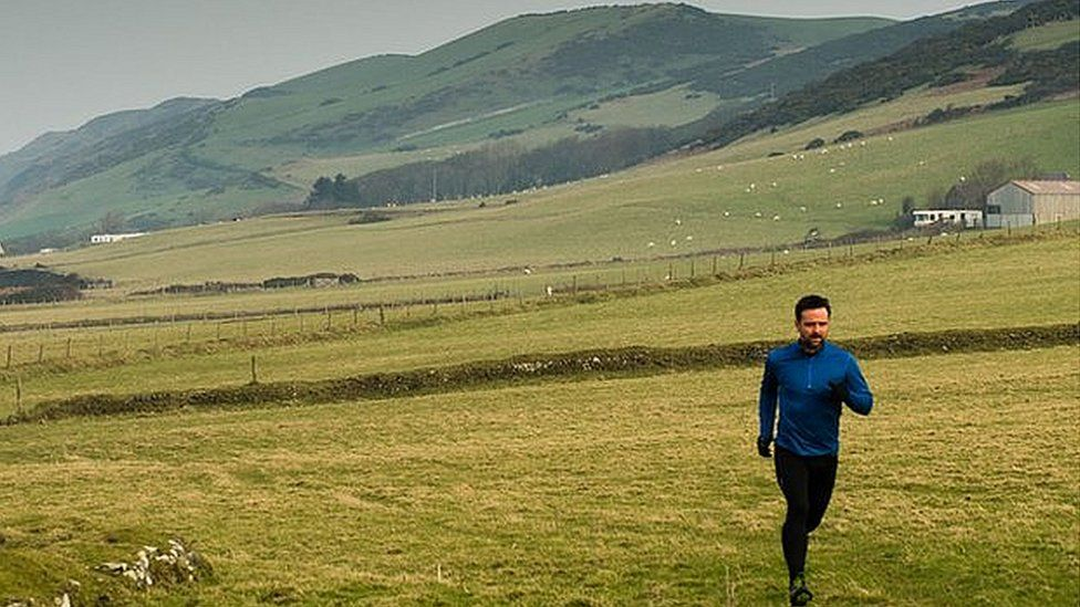 Richard Harrington running in countryside with hilly backdrop