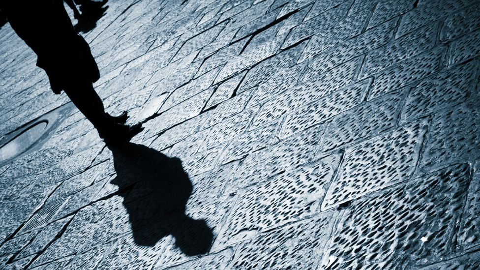 Shadow of man standing on pavement after dark