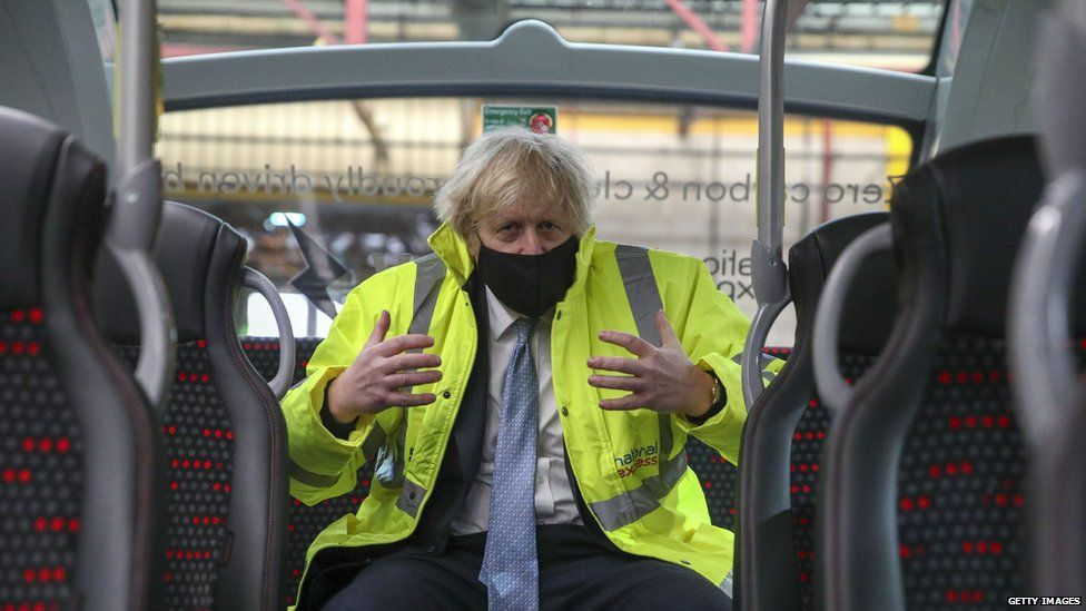 PM Boris Johnson sitting at the back of a bus in Warwickshire