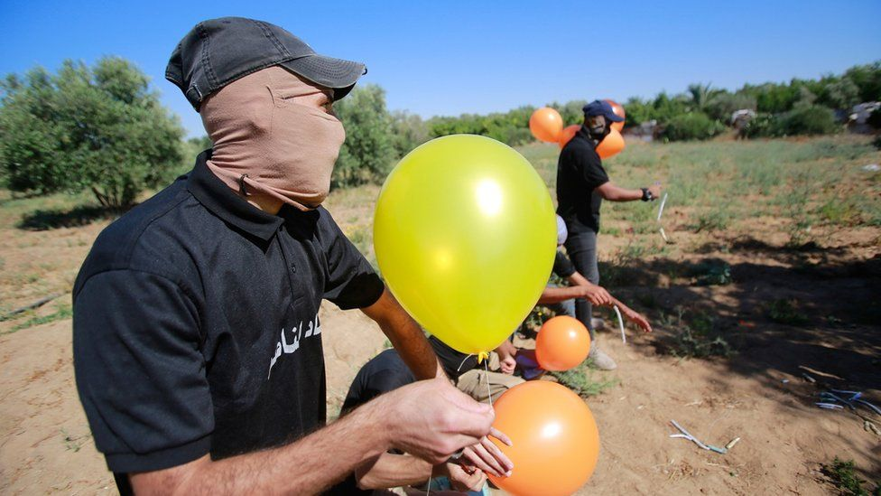 Masked Palestinians launch incendiary balloons from the Gaza Strip towards Israel.