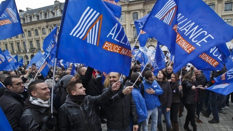 French police officers in Paris carry union flags next to the French justice ministry as part of their protest to demand better working conditions in Paris (14 October 2015)