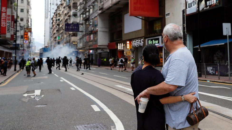 """A couple hugs each other as police fire tear gas into the crowds to disperse anti-national security law protesters during a march at the anniversary of Hong Kong""""s handover to China from Britain in Hong Kong, China"""