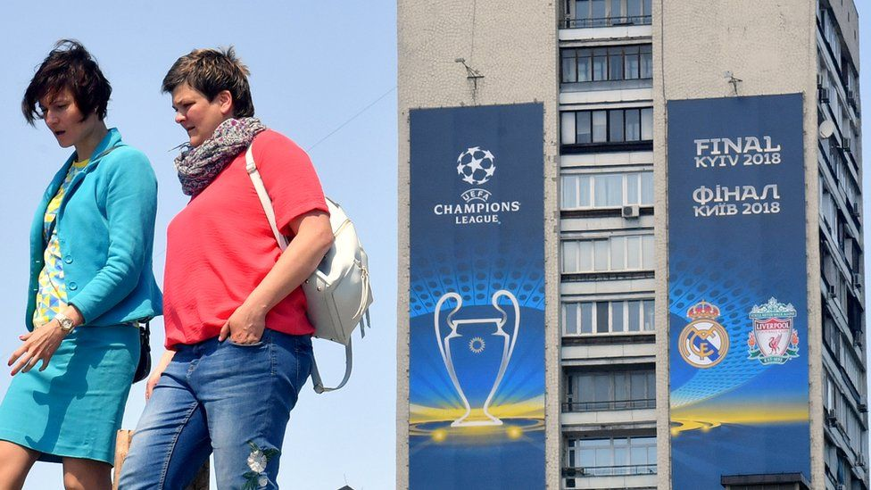 Women walk past a poster of the 2018 UEFA Champions League Final set on a building in Kiev